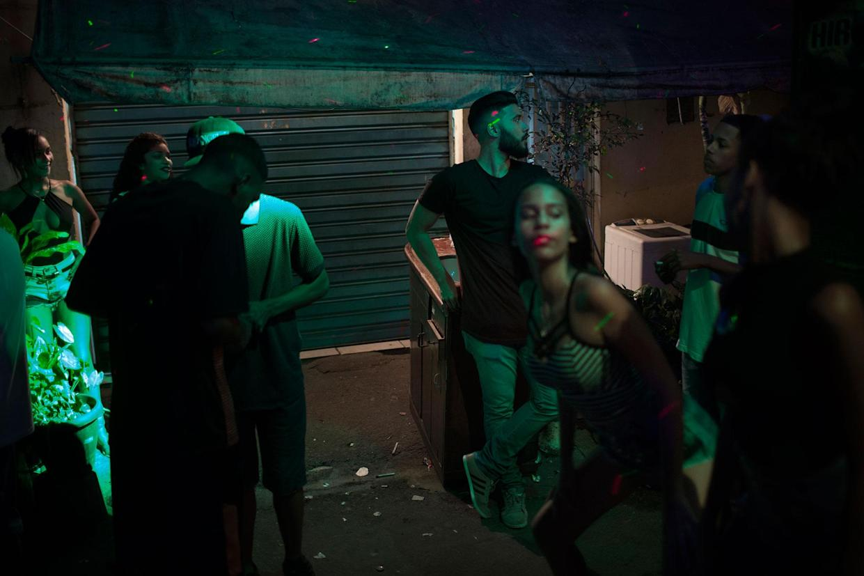 A girl dances to the music at Baile Funk party tin Parque Uniao, a shantytown in Rio de Janeiro, Brazil in August 2016. Nayane says that, in this party, very young girls and boys drink and take drugs. She says she knows a girl, age 11, that already goes to these parties and has sexual intercourse with men. Most of the unions of very young girls with boys she knows are formed during this ball. (Photo: Rafael Fabrés)