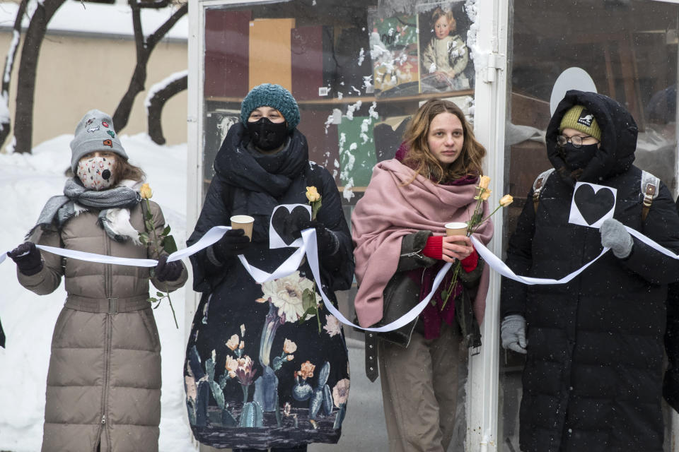 Women hold flowers and a white ribbon as they stand in a line during a rally in support of jailed opposition leader Alexei Navalny and his wife Yulia Navalnaya at Arbat street in Moscow, Russia, Sunday, Feb. 14, 2021. (AP Photo/Pavel Golovkin)
