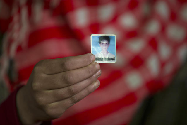 In this Dec. 26, 2018 photo, Maymoona Rashid holds the only photograph she has of her brother Mudassir Rashid Parray in Hajin village, north of Srinagar, Indian controlled Kashmir. Mudassir, who was then 14-years-old, and another teenager walked away from a local soccer pitch in the Kashmiri town of Hajin on a hot day in August, only to return home months later in body bags. Dying with his teammate in an 18-hour firefight in December, Mudassir became the youngest militant slain fighting Indian troops in a three-decade insurgency in Kashmir. (AP Photo/Dar Yasin)