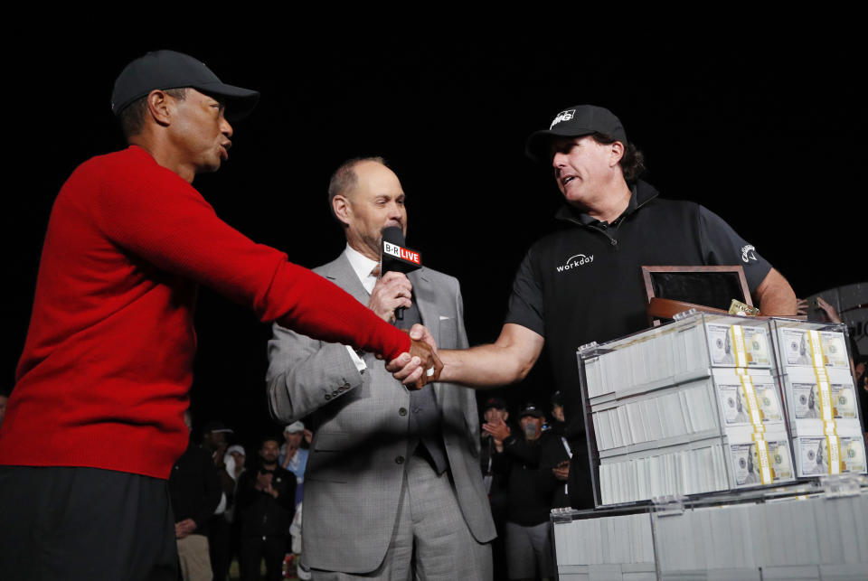 Tiger Woods, left, shakes hands after losing a golf match to Phil Mickelson, right, at Shadow Creek golf course, Friday, Nov. 23, 2018, in Las Vegas. (AP Photo/John Locher)
