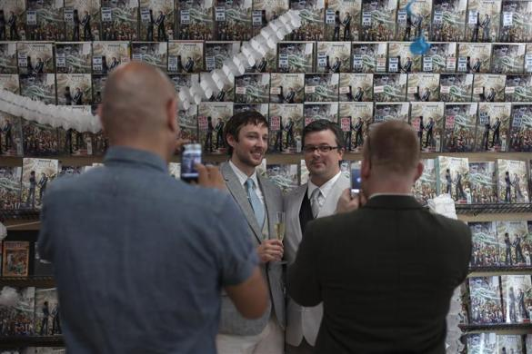 Friends photograph Jason Welker (L) and Scott Everhart after their wedding ceremony at a comic book retail shop in Manhattan, New York June 20, 2012.