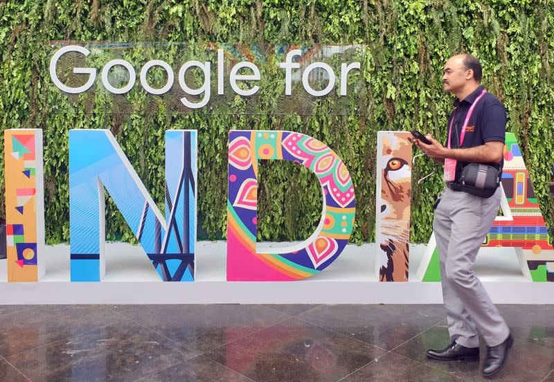 """FILE PHOTO: A man walks past the sign of """"Google for India"""", the company's annual technology event in New Delhi"""