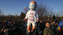 """Anti-vaccination protesters hold a doll with """"I don't want to be a lab rat"""" written on it during a rally outside the parliament building in Bucharest, Romania, Sunday, March 7, 2021. Some thousands of anti-vaccination protestors from across Romania converged outside the parliament building protesting against government pandemic control measures as authorities announced new restrictions amid a rise of COVID-19 infections. (AP Photo/Vadim Ghirda)"""