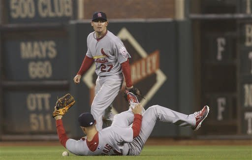 St. Louis Cardinals first baseman Allen Craig, bottom, cannot catch a base hit by San Francisco Giants pitcher Madison Bumgarner as second baseman Tyler Greene (27) looks on during the seventh inning of a baseball game in San Francisco, Wednesday, May 16, 2012. (AP Photo/Jeff Chiu)
