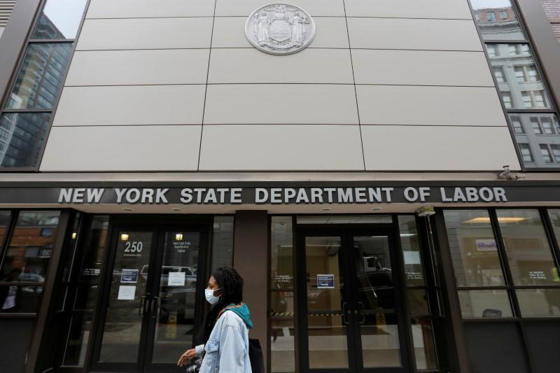 FILE PHOTO: A person walks by the entrance of the New York State Department of Labor offices, which closed to the public due to the coronavirus disease (COVID-19) outbreak in the Brooklyn borough of New York City