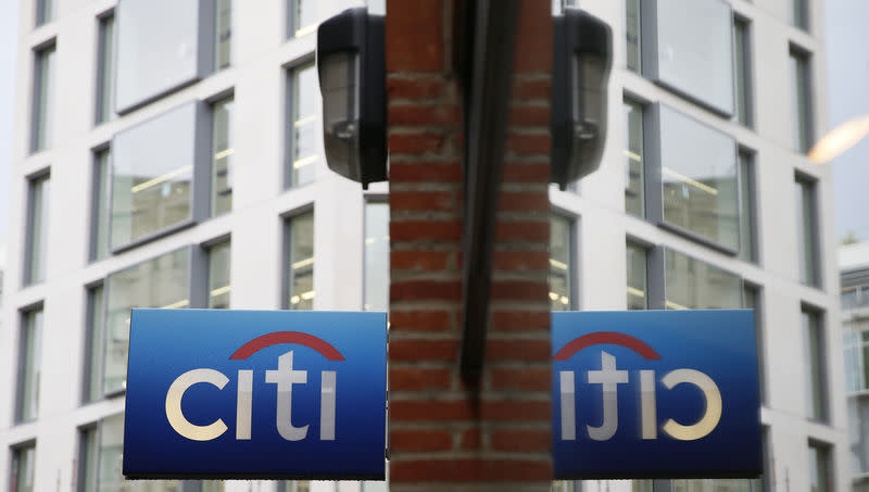 A Citibank sign is reflected in a window in the City of London