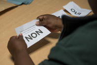 A volunteer counts ballots in a voting station of Noumea, New Caledonia, Sunday, Oct.4, 2020. Voters in New Caledonia, a French archipelago in the South Pacific, were deciding Sunday whether they want independence from France in a referendum that marks a milestone in a three-decade decolonization effort. If voters choose independence, a transition period will immediately open so that the archipelago can get ready for its future status. Otherwise, New Caledonia will remain a French territory. (AP Photo/Mathurin Derel)