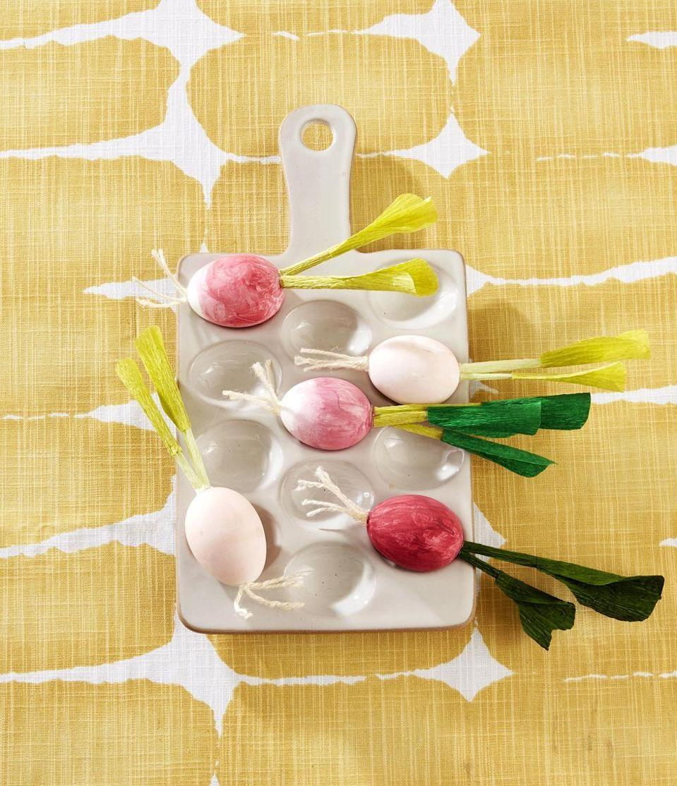 <p>Whip up a batch of eggs that resemble farmer's market fresh radishes by painting three quarters of a blown-out egg with pink paint. Finish the look by using hot glue to attach off-white twine to the bottom as roots, and rolled-up green crepe paper to the top as a stem.</p>