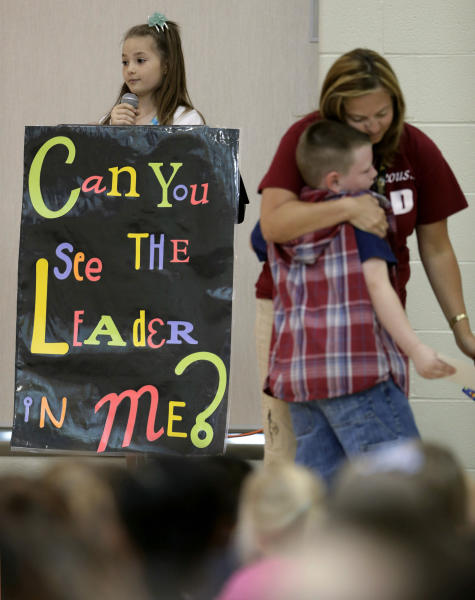 "In this photo taken Friday, Sept. 6, 2013, third-grader Jonathan Kent gets a hug from his teacher Mandy Brown after getting an award during a monthly leadership assembly presided over by fourth-grader Anita Bedworth at Indian Trails Elementary school in Independence, Mo. The school is one of 1,400 nationwide utilizing a program called ""The Leader in Me"" which is based on the late self-help guru Stephen Covey's best-selling ""The Seven Habits of Highly Effective People."" (AP Photo/Charlie Riedel)"