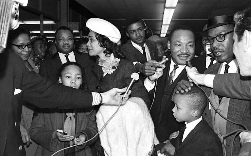Nobel Peace Prize Winner, Dr. Martin Luther King, says a few words as he prepares to board plane to New York on his way tp Oslo. King is accompanied by his wife Coretta, (L). Two of his four children Yolanda, (with mother), and Martin Luther King III, (R), were also on hand with many followers of the integration leader to see him off. | Bettmann Archive