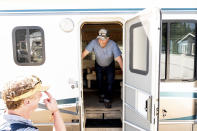 Volunteer firefighter John Hunter looks out from a donated motorhome he received from Woody Faircloth, left, on Sunday, Sept. 5, 2021, in Quincy, Calif. Hunter lost his home and hardware store to the Dixie Fire in August. (AP Photo/Noah Berger)