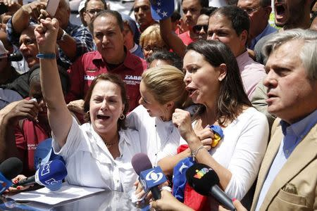 Mitzy de Ledezma (L), wife of arrested Caracas metropolitan mayor Antonio Ledezma, shouts next to Lilian Tintori (C), wife of jailed opposition leader Leopoldo Lopez, and opposition leader Maria Corina Machado (2nd R), during a gathering in support of Ledezma in Caracas February 20, 2015.  REUTERS/Carlos Garcia Rawlins