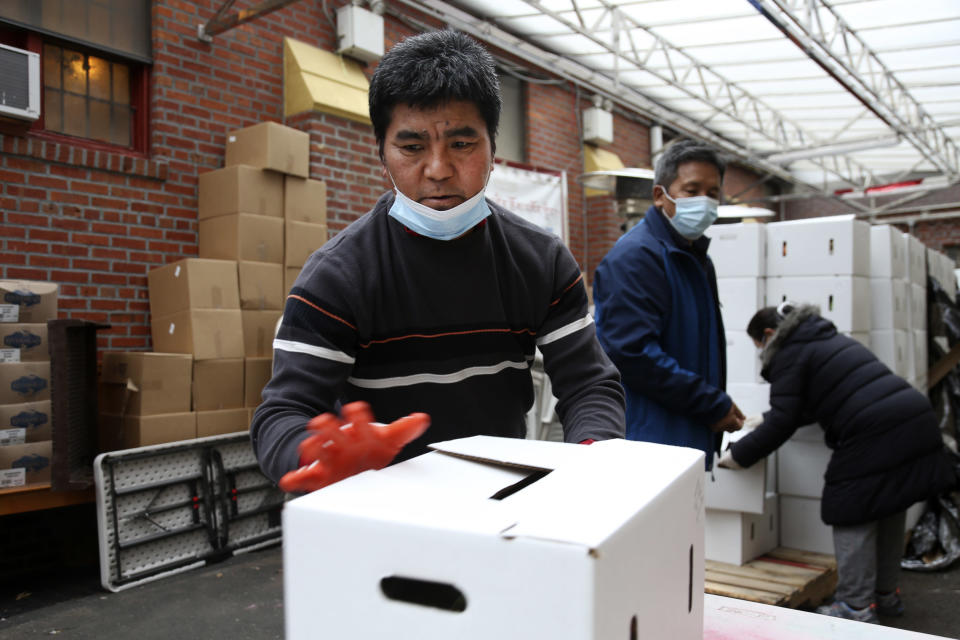 Phurba Sherpa, left, and other volunteers move boxes of food at the United Sherpa Association's weekly food pantry on Friday, Jan. 15, 2021, in the Queens borough of New York. The pantry began in April with a focus on the Nepalese community, international students and families living in the country without permission. (AP Photo/Jessie Wardarski)