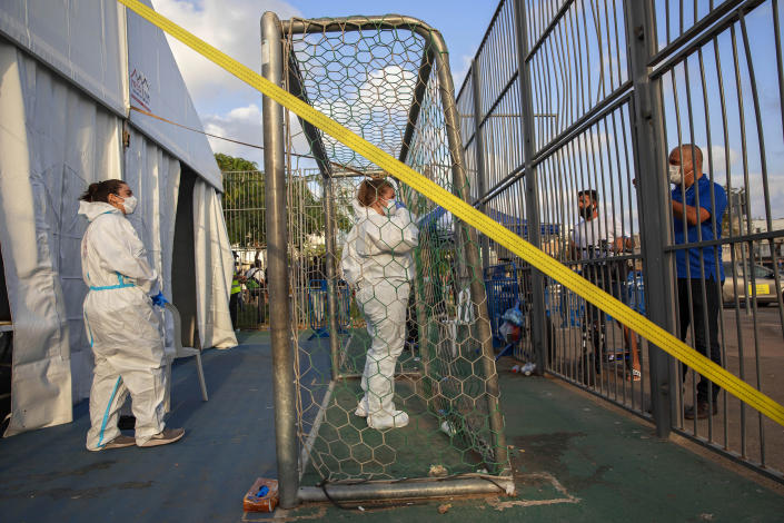 Image: Israeli healthcare workers at a testing center for migrants in Tel Aviv on Monday. (Oded Balilty / AP)