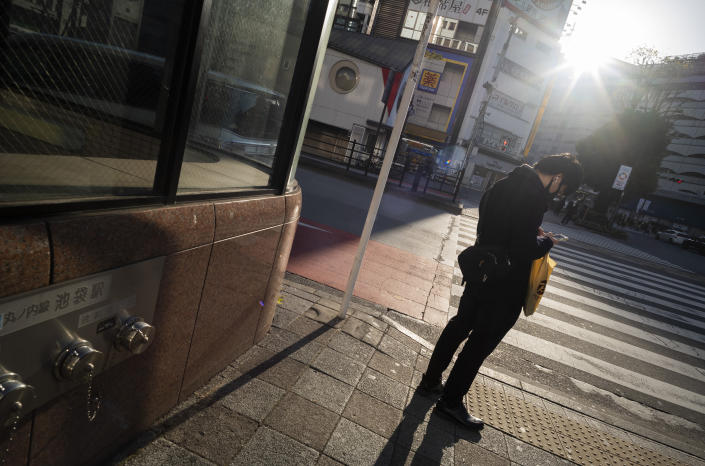 A man wearing a face mask looks at his cellphone while waiting to walk across an intersection during the coronavirus state of emergency in Tokyo on Thursday, Jan. 14, 2021. (AP Photo/Hiro Komae)