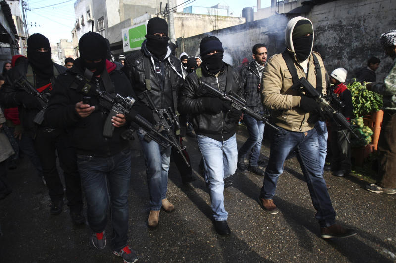 Palestinian members of the Al-Aqsa Martyrs Brigades, a group loyal to Palestinian leader Mahmoud Abbas' Fatah movement march in the Balata refugee camp in the West Bank, Thursday, Jan. 10, 2013. The men were protesting a recent campaign by Abbas to disarm renegade gunmen. The march comes at a time when Israel's president warns of the possibility of renewed Palestinian violence over stalled negotiations with Israel.(AP Photo/Nasser Ishtayeh)