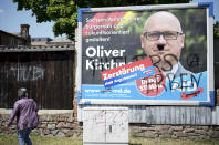 """A vandalized election campaign poster for the far-right Alternative for Germany party showing the party's top candidate, Oliver Kirchner, stands on a road in Saxony-Anhalt's state capital of Magdeburg, Germany, Wednesday, June 2, 2021. The state vote on Sunday, June 6, 2021 is German politicians' last major test at the ballot box before the national election in September that will determine who succeeds Chancellor Angela Merkel. After a mustache and the words """"Hitler's heirs"""" were sprayed on the poster, the party added a sticker reading: 'Destruction instead of arguments?' The AFD election campaign slogan reads: ' Make Saxony-Anhalt safe, close to the citizen and future-oriented'. (AP Photo/Markus Schreiber)"""