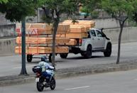 Coffins are seen stacked high on a pick-up truck and trailer as it passes a hospital in Guayaquil, Ecuador
