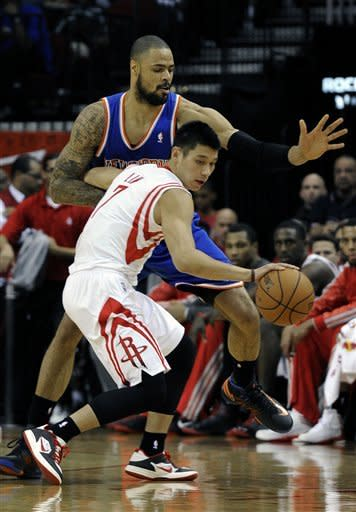Houston Rockets' Jeremy Lin (7) holds New York Knicks' Tyson Chandler at bay in the first half of an NBA basketball game, Friday, Nov. 23, 2012, in Houston. (AP Photo/Pat Sullivan)