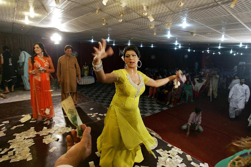 In this Sunday, Oct. 21, 2012, photo, a man, bottom left, offers money to Sonia, 26, a transgender Pakistani, while dancing at the birthday party of her transgender friend, Sana, not pictured, in Rawalpindi, Pakistan. Transgender people live in a tenuous position in conservative Pakistan, where the roles of the sexes are traditionally starkly drawn. Families often push them out of the home when they're young, forcing many to prostitute themselves to earn a living. One role where they are tolerated is as dancers at weddings and other celebrations at which men and women are strictly segregated.(AP Photo/Anjum Naveed)