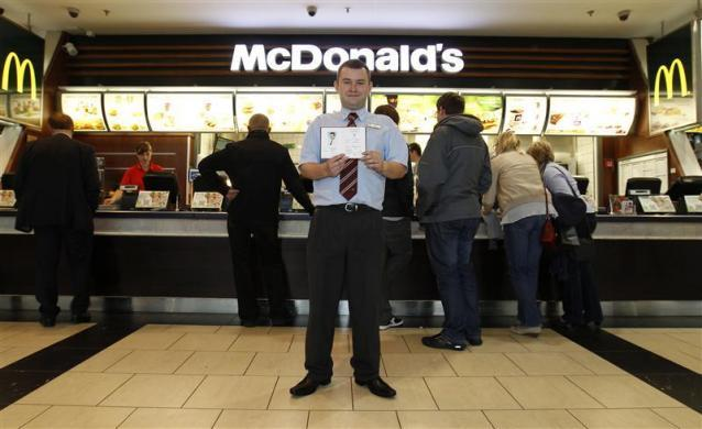 Marcin Lubowicki, a 28 year-old deputy manager of a McDonald's restaurant, poses with his university diploma in front of the fast food chain in the Arkadia shopping mall, Warsaw, May 16, 2012. Lubowicki, who has a degree in Russian language from Warsaw University, has been working for McDonald's since 2007. He is planning to stay in his job.