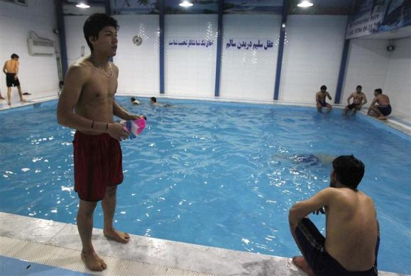 Rohullah Nikpai (L) attends a training session in a swimming pool in Kabul February 16, 2012.