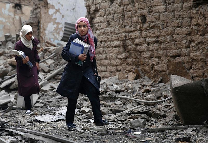 Young women carry books as they walk amid the rubble of destroyed buildings following a reported air strike by Syrian government forces in the rebel-held area of Douma, east of Damascus, on October 29, 2015 (AFP Photo/Sameer al-Doumy)