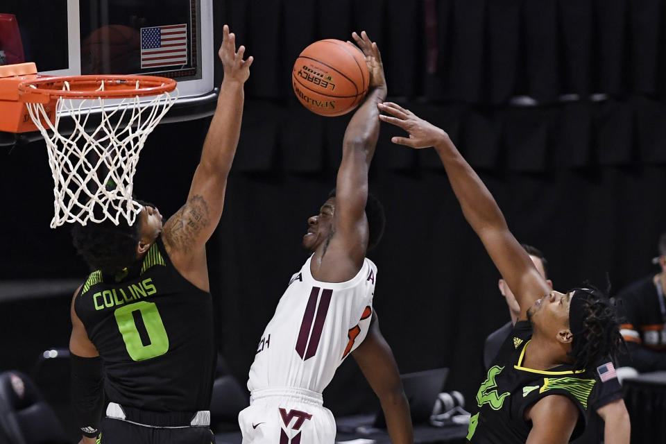 South Florida's Michael Durr, right, fouls Virginia Tech's Nahiem Alleyne, center, as South Florida's David Collins, left, defends in the first half of an NCAA college basketball game, Sunday, Nov. 29, 2020, in Uncasville, Conn. (AP Photo/Jessica Hill)