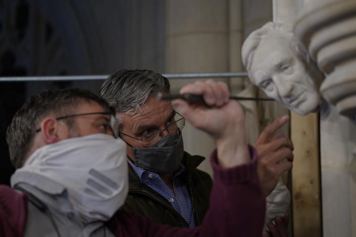 Artist Chas Fagan, right, works to fine tune his sculpture of Holocaust survivor and Nobel Peace Prize winning author Elie Wiesel with stone carver Sean Callahan in the Human Rights Porch of the Washington National Cathedral, Friday, April 16, 2021. Fagan, who created all the sculptures in the Human Rights Porch, worked off photos and videos provided by Wiesel's family to fashion a clay sculpture of Wiesel's head that Callahan and head stonemason Joe Alonso used to make a plaster model. Then Callahan, using specialized calibration equipment, painstakingly carved the image into a small slab of rock that has been sticking out of the wall for years awaiting a fourth face. (AP Photo/Carolyn Kaster)
