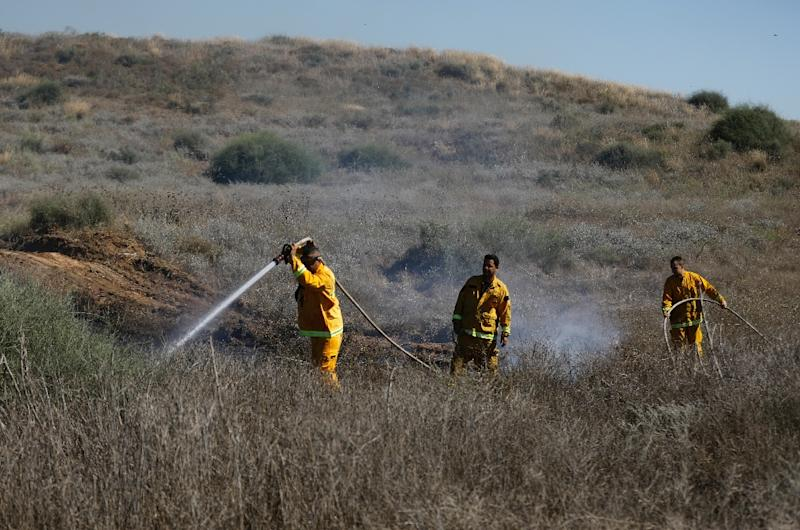 Israeli firefighters extinguish a blaze near the border with the Gaza Strip on June 20, 2018, after it was set off by incendiary kites flown from the Palestinian enclave (AFP Photo/Menahem KAHANA)