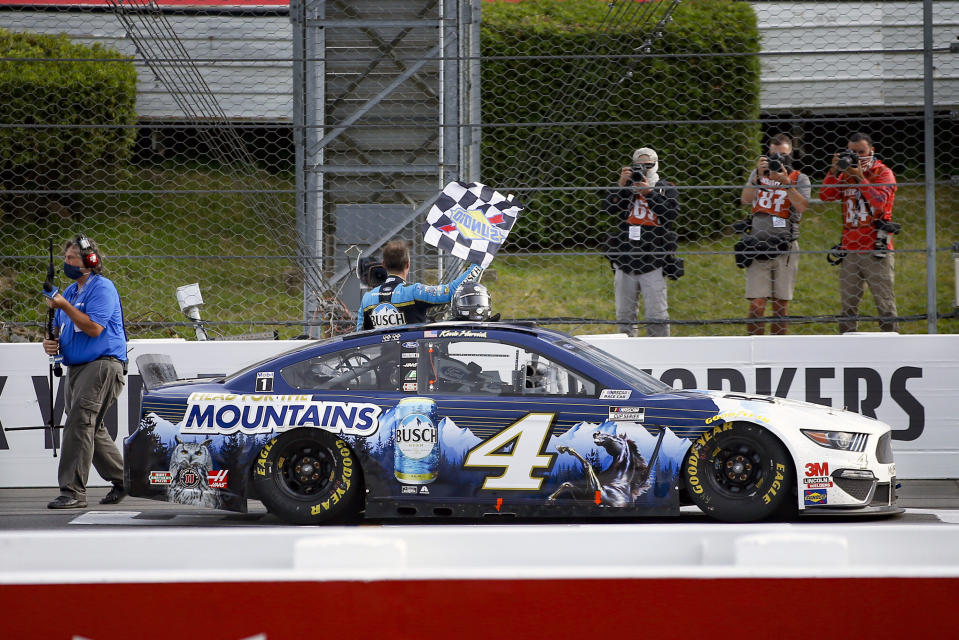Kevin Harvick waves a checker flag for photographers after winning the NASCAR Cup Series auto race at Pocono Raceway, Saturday, June 27, 2020, in Long Pond, Pa. (AP Photo/Matt Slocum)