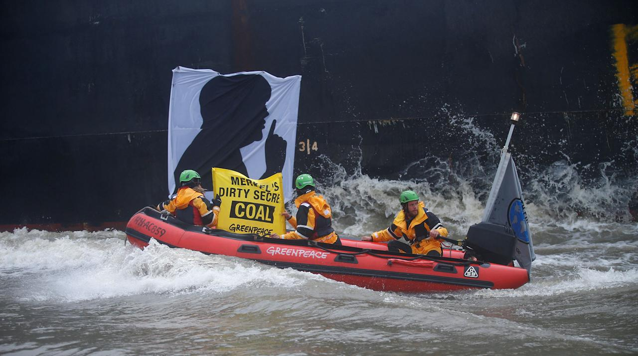 <p>Greenpeace activists ride along a banner with a silhouette of German Chancellor Angela Merkel onto the Golden Opportunity ship carrying coal as part of protests ahead of the upcoming G20 summit, in Hamburg Harbour, Germany July 2, 2017. (Hannibal Hanschke/Reuters) </p>
