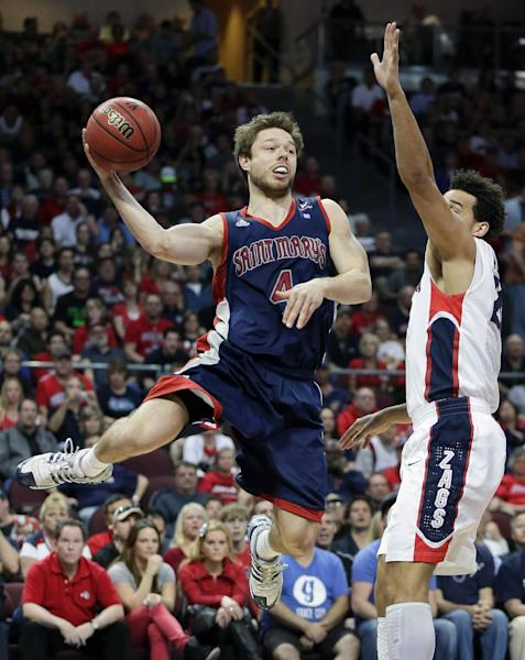 Saint Mary's Matthew Dellavedova (4) passes the ball off against Gonzaga's Elias Harris during the first half of the West Coast Conference tournament championship NCAA college basketball game, Monday, March 11, 2013, in Las Vegas. (AP Photo/Julie Jacobson)