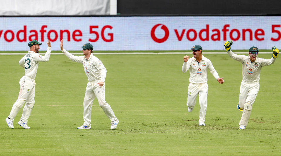 Australia's Matthew Wade, left, is congratulated by teammate Steve Smith on a catch to dismiss India's Ajinkya Rahane as David Warner and Tim Paine react during play on day three of the fourth cricket test between India and Australia at the Gabba, Brisbane, Australia, Sunday, Jan. 17, 2021. (AP Photo/Tertius Pickard)