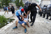 Police detain a soccer outside the presidential palace where Diego Maradona is lying in Buenos Aires, Argentina, Thursday, Nov. 26, 2020. The Argentine soccer great who led his country to the 1986 World Cup title died of a heart attack at his home Wednesday at the age of 60. (AP Photo/Natacha Pisarenko)