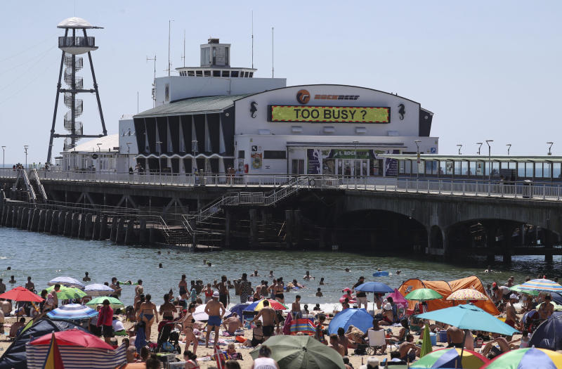 Crowds gather on the beach in Bournemouth, England, Thursday June 25, 2020, as coronavirus lockdown restrictions have been relaxed. According to weather forecasters Thursday could be the UK's hottest day of the year, so far, with scorching temperatures forecast to rise even further. (Andrew Matthews/PA via AP)