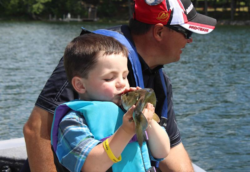 In this photo made Wednesday, June 26, 2013 in Nevis , Minn., Bobby Tufts, the 4-year-old mayor of Dorset, Minn., kisses a fish that his guide, Jason Durham, caught on Lake Belle Taine. The fish, the first was released. Bobby was only 3 when he won election last year as mayor of Dorset (population 22 to 28, depending on whether the minister and his family are in town). Dorset, which bills itself as the Restaurant Capital of the World, has no formal city government. (AP Photo/Jeff Baenen)