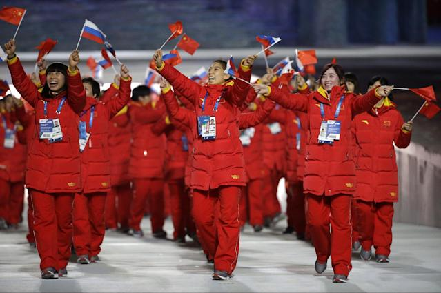 Members of the Chinese team wave Russian and Chinese flags as they arrive during the opening ceremony of the 2014 Winter Olympics in Sochi, Russia, Friday, Feb. 7, 2014. (AP Photo/Mark Humphrey)