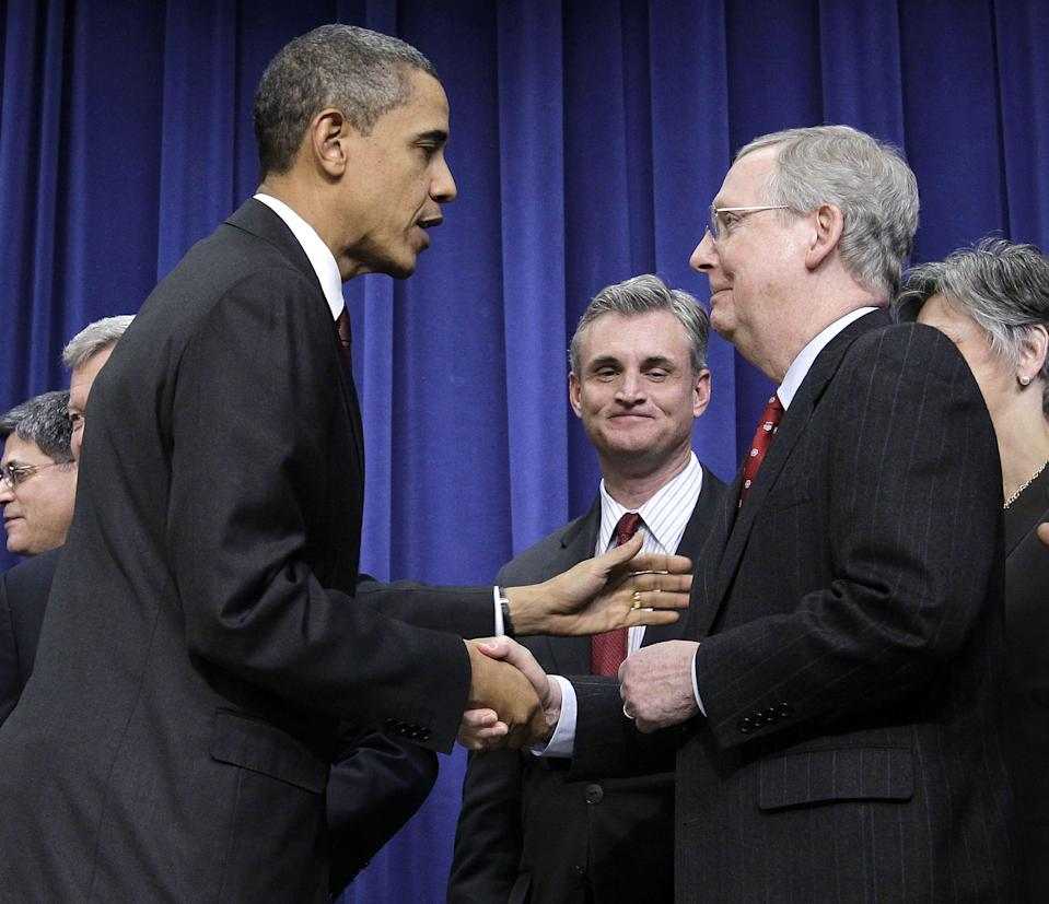 President Barack Obama, left, shakes hands with Senate Republican Leader Mitch McConnell, R-Ky., right, after signing the $858 billion tax deal into law in a ceremony in the Eisenhower Executive Office Building on the White House complex, Friday, Dec. 17, 2010 in Washington.