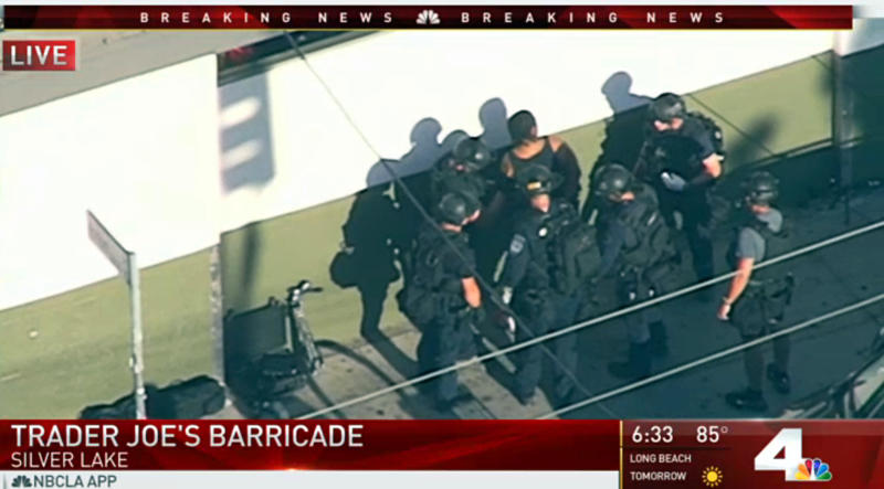 In this image from video provided by KNBC-TV, officers take a suspect into custody outside a Trader Joe's supermarket in the Silver Lake district of Los Angeles Saturday, July 21, 2018. (KNBC-TV via AP)