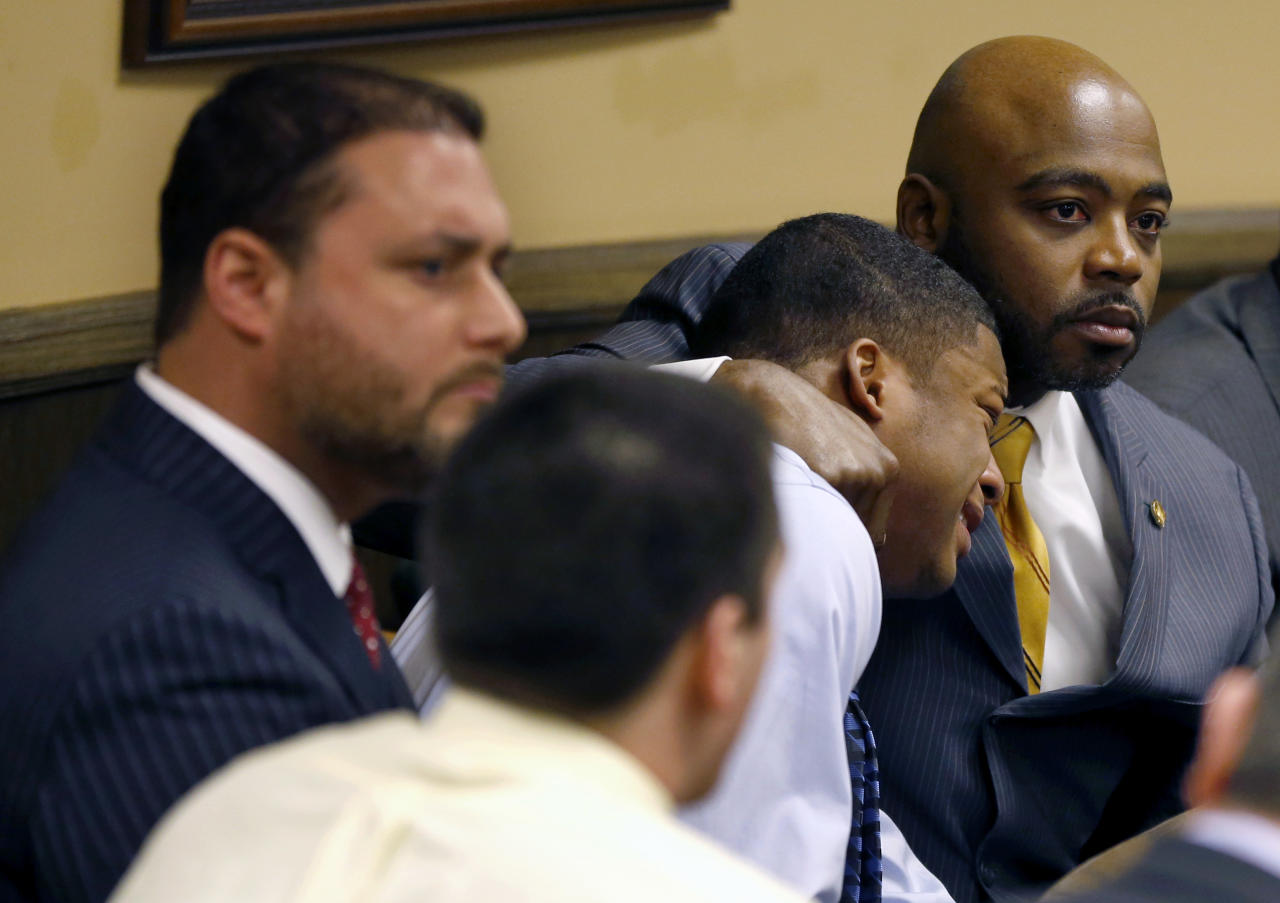 Defense attorney Walter Madison, right, holds his client, 16-year-old Ma'Lik Richmond, second from right, while defense attorney Adam Nemann, left, sits with his client Trent Mays, foreground, 17, as Judge Thomas Lipps pronounces them both delinquent on rape and other charges after their trial in juvenile court in Steubenville, Ohio, Sunday, March 17, 2013. Mays and Richmond were accused of raping a 16-year-old West Virginia girl in August 2012. (AP Photo/Keith Srakocic, Pool)