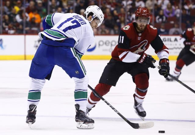 Vancouver Canucks center Nic Dowd (17) passes the puck behind him as Arizona Coyotes left wing Brendan Perlini (11) looks to intercept the puck during the first period of an NHL hockey team Sunday, March 11, 2018, in Glendale, Ariz. (AP Photo/Ross D. Franklin)