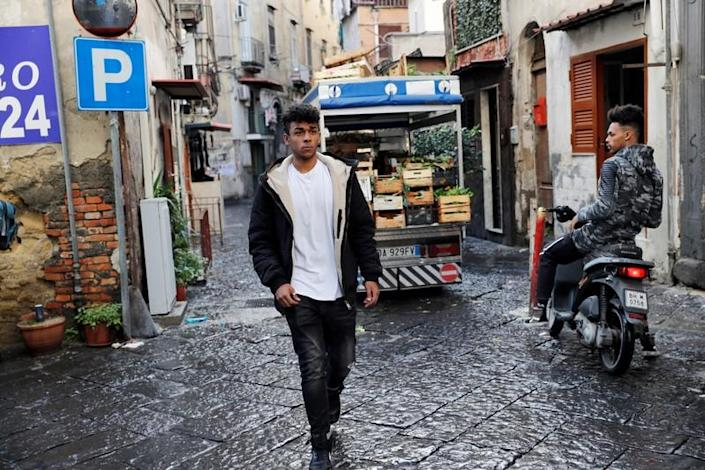 Nico Rodrigues, 21, walks on the street, close to the Santa Maria della Sanita Basilica in the Rione Sanita neighbourhood, in Naples