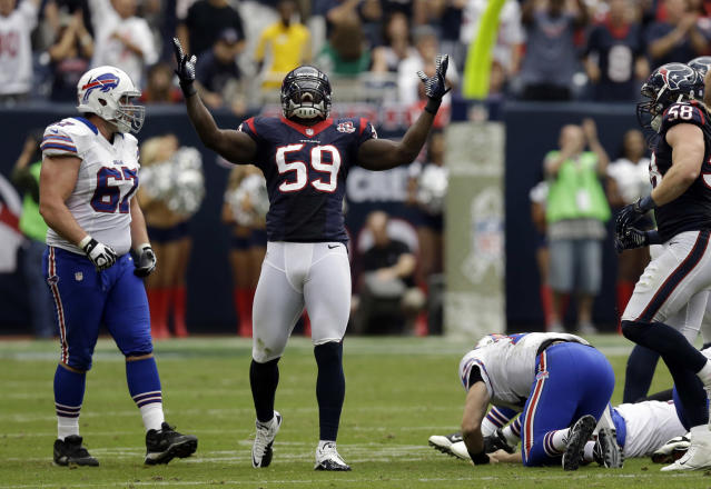 Houston Texans linebacker Whitney Mercilus (59) celebrates after hitting Buffalo Bills quarterback Ryan Fitzpatrick, right, causing a fumble in the fourth quarter of an NFL football game on Sunday, Nov. 4, 2012, in Houston. Houston recovered the fumble. Bills' Andy Levitre, left, looks on. (AP Photo/Eric Gay)