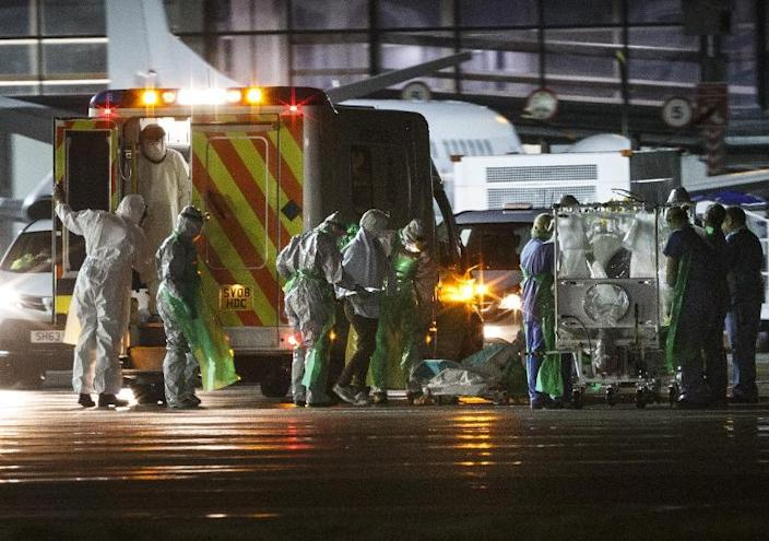 A healthcare worker (centre) who was diagnosed with Ebola after returning from Sierra Leone is walked from an ambulance and put into a quarantine tent trolley before being wheeled into a plane at Glasgow airport bound for London on December 30, 2014 (AFP Photo/-)