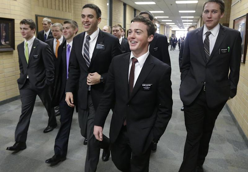 FILE - In this Jan. 8, 2013, file photo, Mormon missionaries walk through the halls at the Missionary Training Center in Provo, Utah. Mormon missionaries will soon spend less time knocking on doors and more time chatting online with potential converts after leaders with The Church of Jesus Christ of Latter-day Saints announced Sunday, June 23, 2013 that it's critical to adapt to a changing world in which many people prefer to connect over social media. (AP Photo/Rick Bowmer, File)