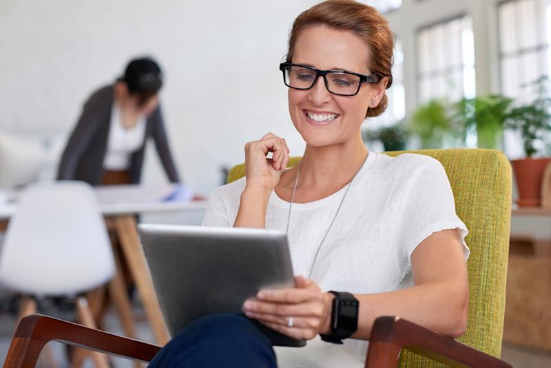 Happy smiling businesswoman looking at portable tablet in creative office