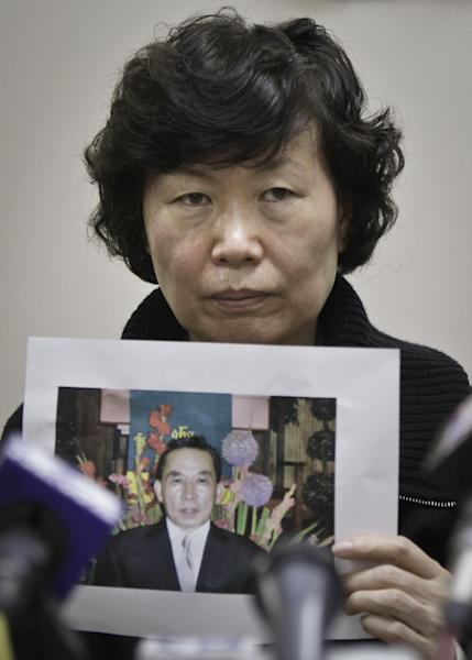 Serim Han holds a picture of her husband Ki-Suck Han during a news conference on Wednesday, Dec. 5, 2012 in New York. A homeless man was arrested Wednesday in the death of Ki-Suck Han, who was pushed onto the tracks and photographed just before a train struck him. (AP Photo/Bebeto Matthews)