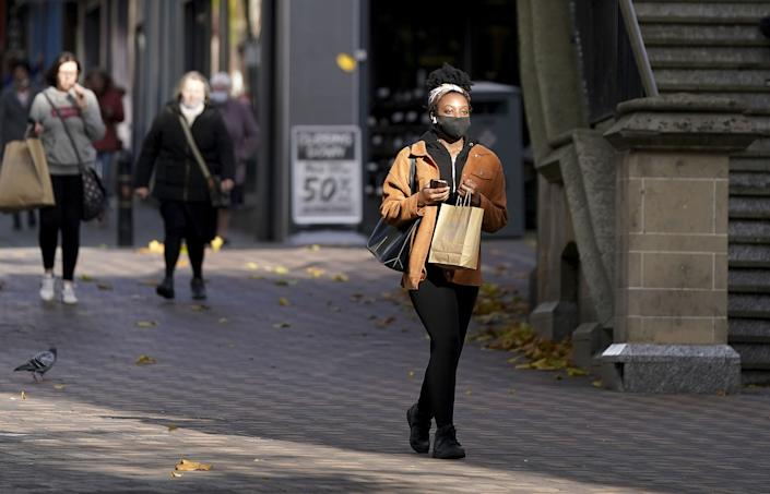 A shopper wears a face mask in Nottingham, where Tier 3 coronavirus restrictions will come into force at midnight.