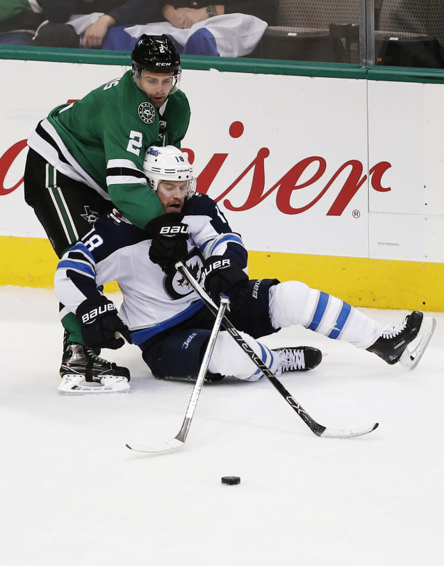 Dallas Stars defenseman Dan Hamhuis (2) and Winnipeg Jets forward Bryan Little (18) battle for the puck during the second period of an NHL hockey game, Saturday, Feb. 24, 2018, in Dallas. (AP Photo/Brandon Wade)